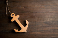 Wooden toy ancor on dark wooden background Stock Photos