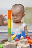 Wooden toy blocks. A chinese child is playing with wooden toy blocks in home Royalty Free Stock Photos