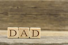 Wooden toy blocks spelling DAD with with wooden background Stock Images
