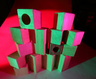 Wooden toy bricks in colored light Royalty Free Stock Images
