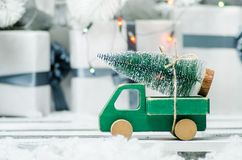 Wooden toy car carrying a christmas tree on shiny lights background.  Stock Photo