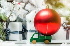 Wooden toy car with christmas ball red decoration on a background of shining lights.  Stock Photos