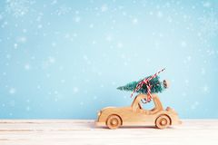 Wooden toy car with Christmas tree on the roof on a blue backgro. Wooden toy car with Christmas tree on the roof on blue background with a snowfall. Christmas Royalty Free Stock Image