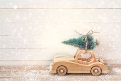 Wooden Toy Car with Christmas tree on the roof on a wooden table. Christmas background. Holidays card. Copy space Stock Images