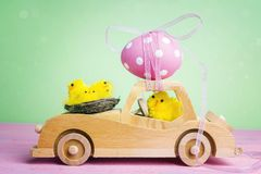 Wooden toy car with Easter egg on the roof and chick driver. Wooden toy car with Easter egg on the roof and chick driver on green background Stock Photos
