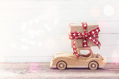 Wooden toy car with a gift box on the roof. White wooden backgro Royalty Free Stock Images