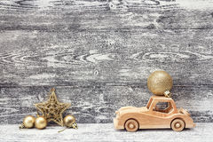 Wooden toy car with golden Christmas ball on the roof. Gray wood Stock Image