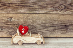Wooden toy car with a heart on a background of old boards. Stock Photo