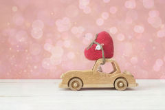 Wooden toy car with heart on the roof on a pink background. Plac. Wooden toy car with heart on the roof on a pink background. Valentine`s Day background. Place Stock Photo
