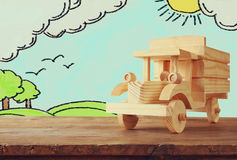 Wooden toy car over table and landscape sketch background Royalty Free Stock Photo
