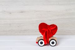 Wooden toy car with red heart. On grey background Royalty Free Stock Image