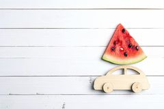 Wooden toy car with slice of watermelon on the roof on white woo royalty free stock image