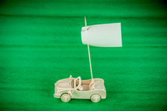 Wooden toy car with white flag. On green background Royalty Free Stock Photography