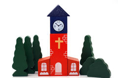 Wooden toy church. Church made of wooden blocks with door, cross and clock painted on it with white paint. The trees and bushes around are also made of wood Royalty Free Stock Photography