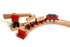 Wooden toy colored train. Wooden toy with magnet crane plunges into the wagon unit, which stands on railroad isolated on white background Royalty Free Stock Photo