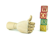 Wooden toy cubes are used to create the word work. Royalty Free Stock Image