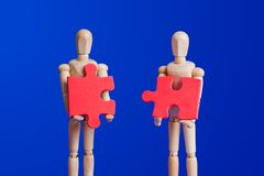 Wooden toy figures with puzzle on blue. Background royalty free stock image