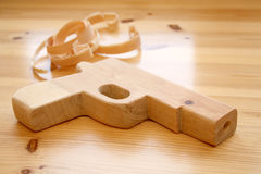 Wooden toy gun with wood shavings. Wooden toy gun and wood shavings on wooden table Stock Image