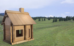 Wooden toy house on a background of nature. Designer wooden toy house on a background of nature Stock Photo