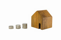 Wooden toy house with coins concept of dearness of habitation Royalty Free Stock Photography