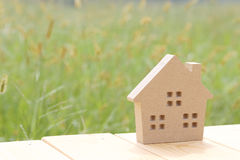 Wooden toy house. On green grass background Stock Photo