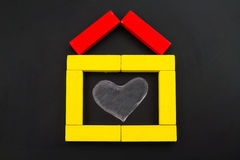 Wooden toy house with heart inside Stock Photos