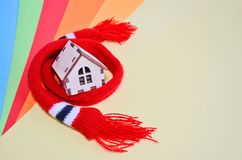 Wooden toy house in a red scarf on a rainbow colored background, warm house, insulation of house, copyspace royalty free stock image