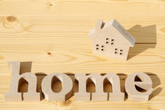 Wooden toy house and word. On table Royalty Free Stock Photography
