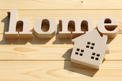Wooden toy house and word. On table Royalty Free Stock Photo