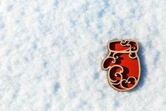 Wooden toy mitten in the snow Stock Photos