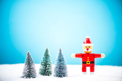 Wooden toy Santa Claus in miniature forest and snow Royalty Free Stock Photo