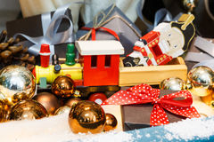 Wooden toy train as christmas gift with shiny baubles, holiday background Royalty Free Stock Photo