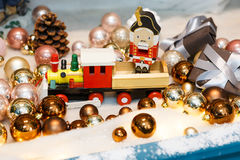 Wooden toy train as christmas gift with shiny baubles, holiday background Stock Images