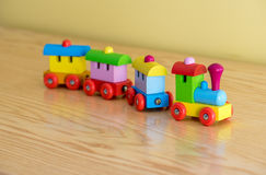 Wooden toy train with colorful blocs. Isolated on a wooden background royalty free stock photography
