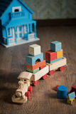 Wooden toy train and doll house. Wooden train and doll house on the floor with vintage wallpaper on background royalty free stock photography