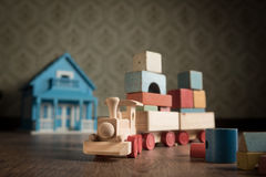 Wooden toy train and doll house. Wooden train and doll house on the floor with vintage wallpaper on background stock image