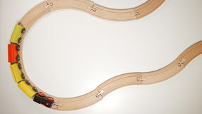 Wooden toy train move on curve wooden railways stop motion. TOP VIEW: Wooden toy train move on curve wooden railways stop motion stock footage