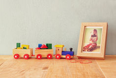 Wooden toy train over wooden table next to photo frame with kid's old photography.  Royalty Free Stock Photos