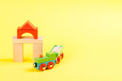 Wooden toy train set on tracks on yellow background. Wooden toy train set on tracks on the yellow background Royalty Free Stock Image