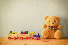 Wooden toy train and teddy bear over wooden floor. retro filtered Stock Photo