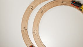 Wooden toy trains move on round wooden railways stop motion stock video