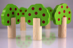 Wooden toy trees. With red apple dots stock photo