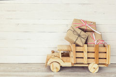 Wooden toy truck with gift boxes in the back on a white wooden b Stock Image
