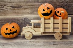 Wooden toy truck with Halloween pumpkins in the back on a background of wooden boards.