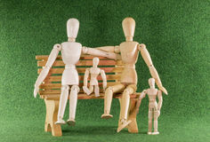 Wooden toys as family on bench Royalty Free Stock Image
