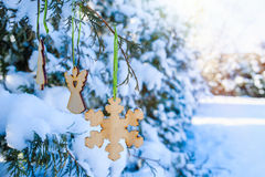 Wooden toys hang on a snow-covered Christmas tree in the park in winter Royalty Free Stock Image