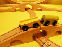 Wooden toys train set. An image of a wood toy train set, with railway lines set up to form curved rail lines and bridges.  Shown with two magnetic wagons of Royalty Free Stock Images