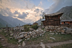 Wooden traditional house with rock wall during sunset at mountain top. Royalty Free Stock Photos