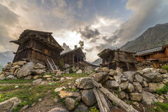 Wooden traditional house with rock wall during sunset at mountain top. Stock Photography