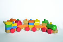 Wooden train, baby toy. Wooden train with locomotive and wagons, assembled with colored blocks,  on white background. part of a series Stock Image